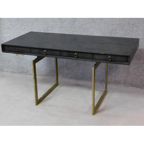134 - A contemporary designer writing table with ebonised top and four drawers on heavy brass pedestal bas...