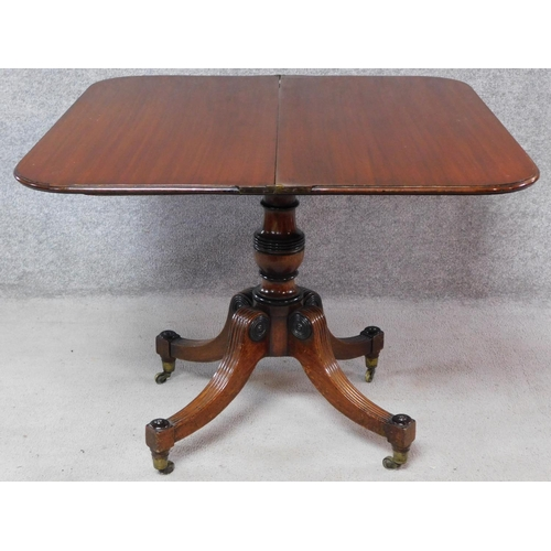 172 - A Regency mahogany fold over top tea table on quadruped reeded supports terminating in brass casters...