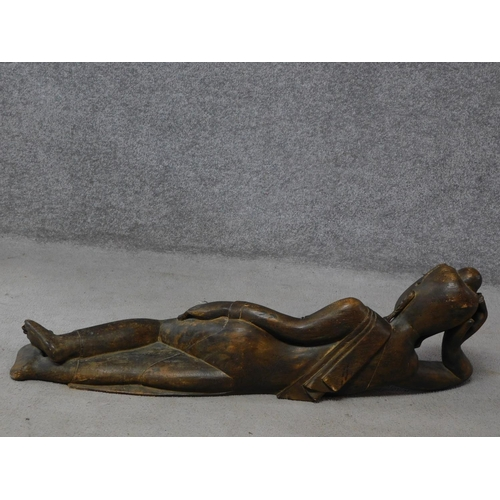90 - An early to mid 20th century Burmese carved hardwood reclining Buddha. With intricately carved detai...
