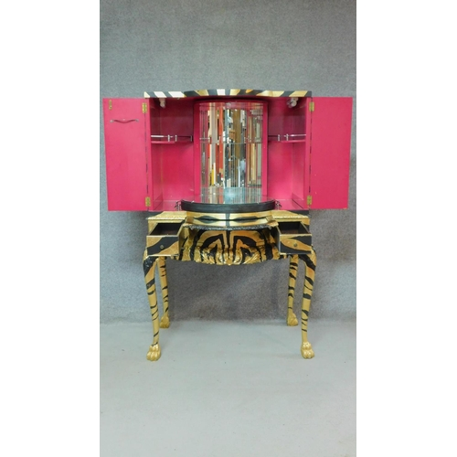 325 - A mid 20th century drinks cabinet fitted revolving glazed interior with later painted tiger stripes....