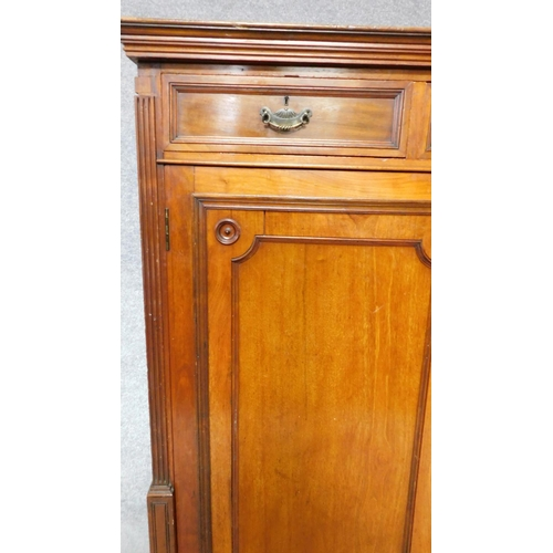 274 - A 19th century mahogany press cupboard with three frieze drawers over panel doors enclosing linen sl...