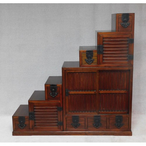 168 - A Chinese hardwood three section cabinet fitted with an arrangement of identical cupboards to each s...