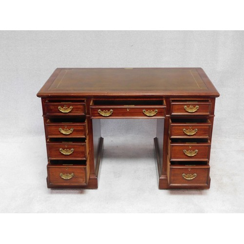 169 - An early 20th century mahogany pedestal desk with inset tooled leather top above an arrangement of n...