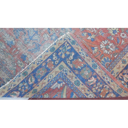 249 - A Persian carpet with allover scrolling foliate decoration on a burgundy ground contained within nat...