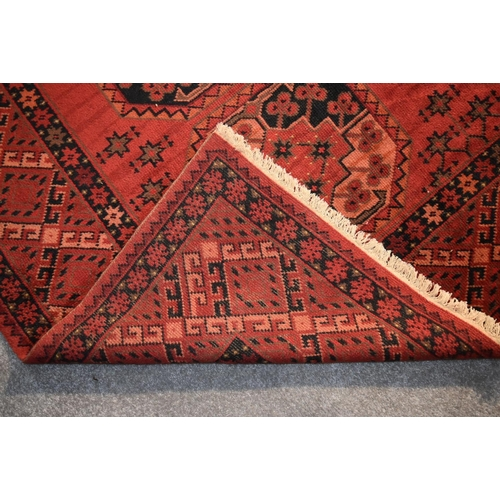 267 - An Afghan Bokhara carpet with  repeating tauk nuska gul design on a burgundy field within geometric ...