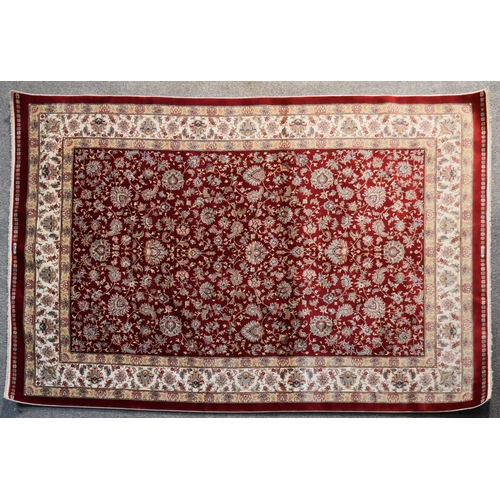 268 - A Persian hand tufted silk rug with repeating floral motifs on burgundy ground within foliate multi ...