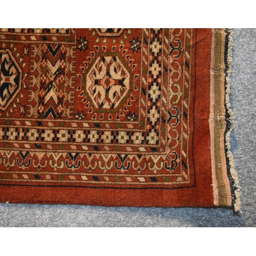 269 - A pure wool Bokhara carpet with repeating gul motifs on burgundy ground within stylised geometric bo...