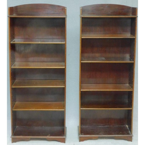 215 - A pair of Edwardian mahogany tall open bookcases with arched backs and adjustable shelves on shaped ...