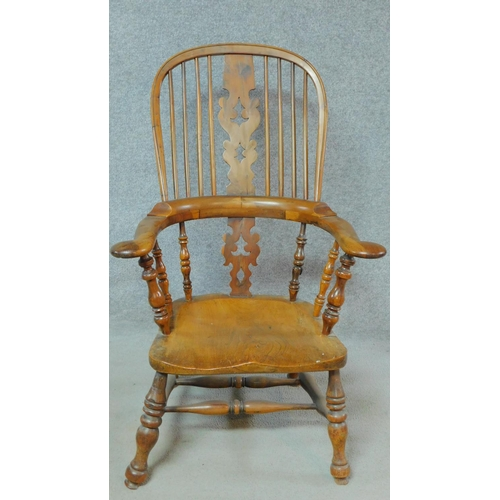 2 - An antique country Windsor armchair with yew wood hooped back, spindles, pierced splat and arms with...
