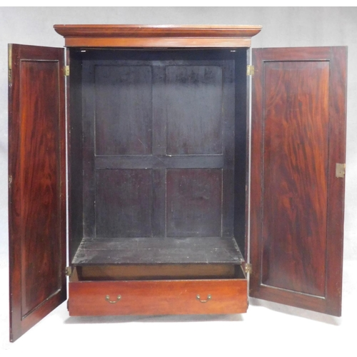 21 - An early 19th century figured mahogany wardrobe with stepped moulded pediment above panel doors encl...