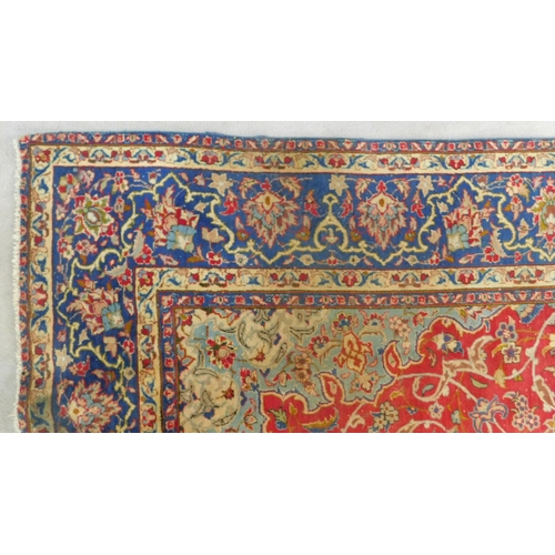 126 - An antique Isfahan carpet with double central medallions on burgundy field with all over scrolling v...