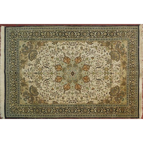 127 - A silk Kashan rug with double medallions of scrolling flower and vine decoration on biscuit field wi...