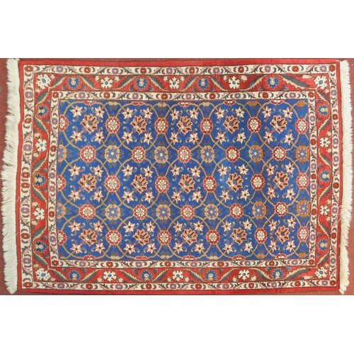 128 - A Veramin Mina Khani style rug with repeating scrolling vine and floral decoration on a deep indigo ...