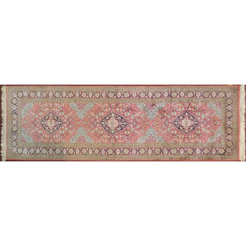 129 - A Persian part silk runner with repeating triple medallions and scrolling floral decoration on a rou...