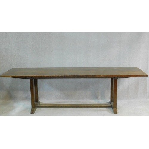 48 - An oak refectory style dining table on chamfered stretchered square section supports on platform bas...