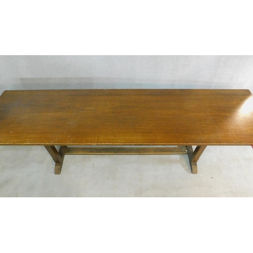 49 - An oak refectory style dining table on stretchered chamfered square section supports on platform bas...