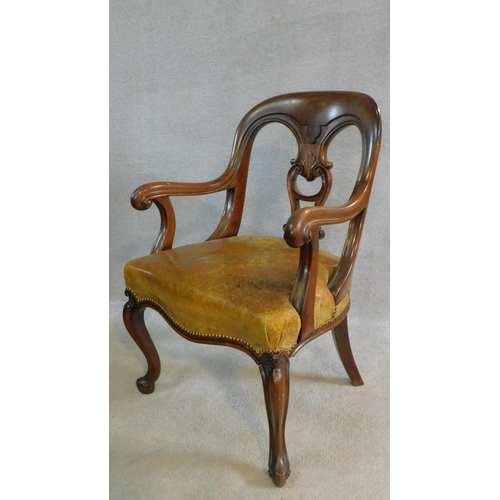 11 - A mid Victorian mahogany desk chair with carved scrolling arms and stuffover leather upholstered and...