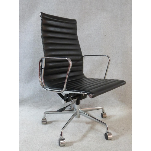 149 - A Charles and Ray Eames Aluminium Group style office desk armchair in black ribbed leather upholster...