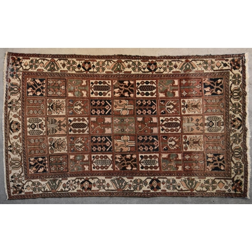 137 - A Persian Bakhtiar carpet with stylised floral panels repeating across the field within stylised pal...
