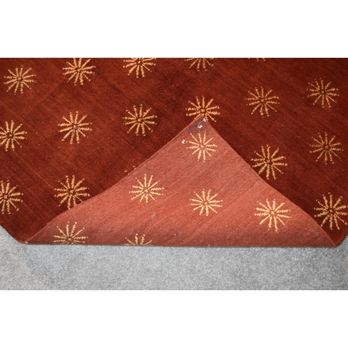 138 - A silk and wool rug with repeating geometric flowerhead design on a burgundy field. L.237x170cm...