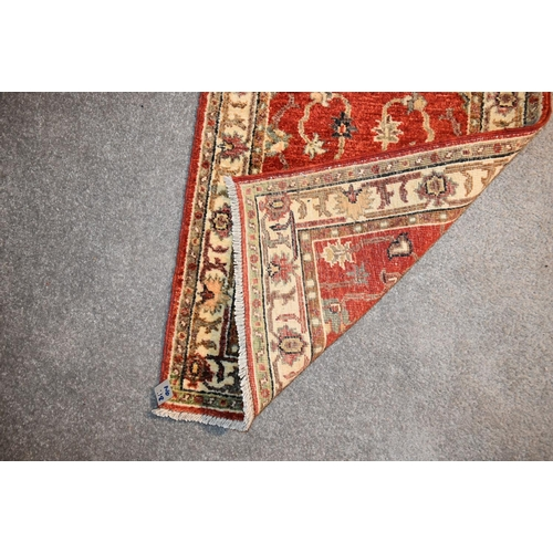 139 - A Ziegler runner with allover scrolling floral design on a deep red field. L.335x60cm...