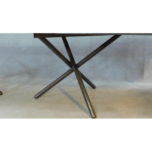 82 - A contemporary twin pedestal ebonised dining table on metal framed tripod supports with extra leaf, ...