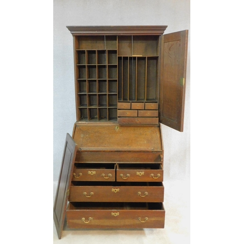 184 - A Georgian country oak bureau bookcase with upper section fitted with fielded panel doors enclosing ...