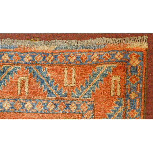 180 - A Kazak rug with central medallion on azure ground within a pale burgundy field and stylised geometr...
