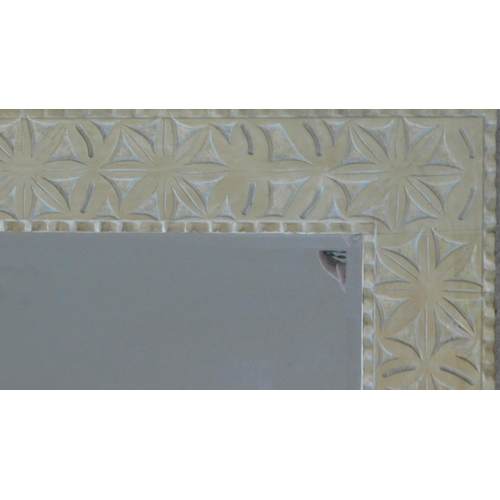 63 - A vintage wall mirror in limed and carved frame fitted with bevelled plate. 122x92cm