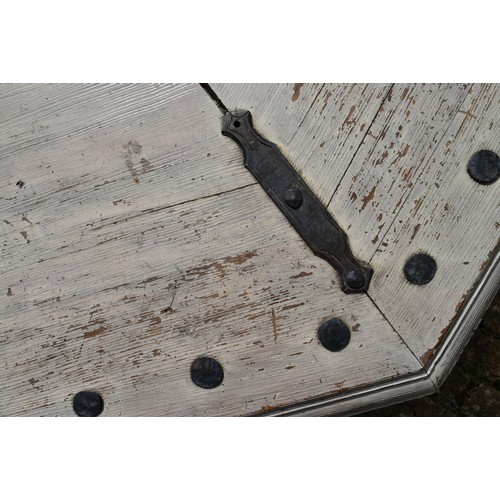 28 - An Octagonal distressed painted wood and iron bound garden bench on platform base. H.50xW.120cm