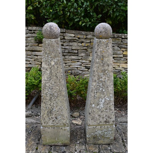 29 - A pair of large weathered reconstituted stone garden obelisks topped with removable spheres. H.132cm...