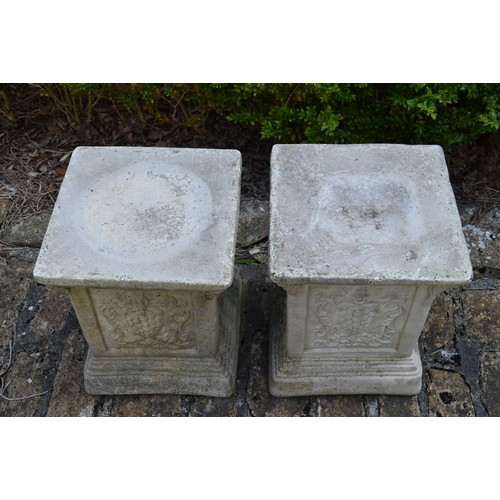 30 - A pair of stepped garden plinths with armorial decoration. H.42xW.34cm