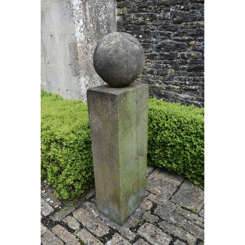 33 - A carved stone garden plinth with weathered spherical finial. H.140cm