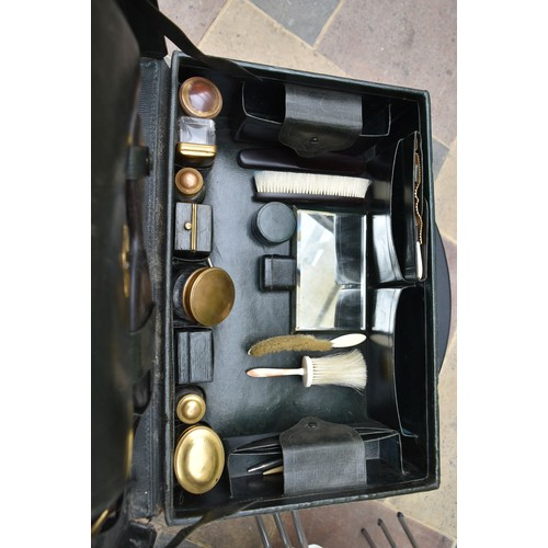 64 - An early 20th century leather travelling gentleman's dressing case, well fitted with a wide collecti...