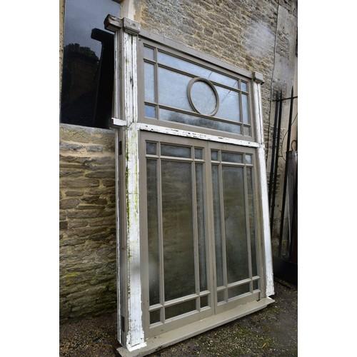 128 - A large painted hardwood window frame of twenty nine double glazed panels with stained glass corner ...
