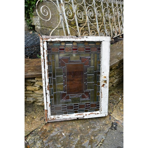 130 - A pair of staincoloured etched and leaded glazed window frames and a similar window in circular fram...