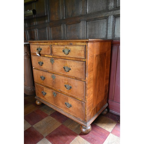 81 - An early Georgian walnut, crossbanded and featherbanded chest of two short over three long graduated...