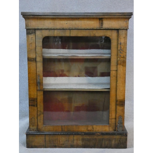 69 - A Victorian figured walnut pier cabinet with satinwood inlaid frieze and ormolu mounts on plinth bas...