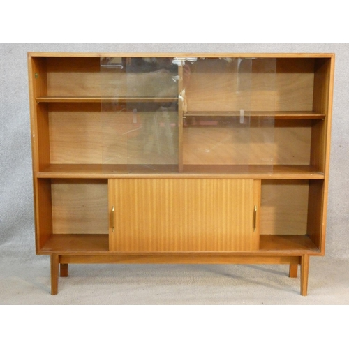 111 - A 1960's vintage teak Beaver and Tapley Multi Width display cabinet on shaped splay supports. H.107 ...