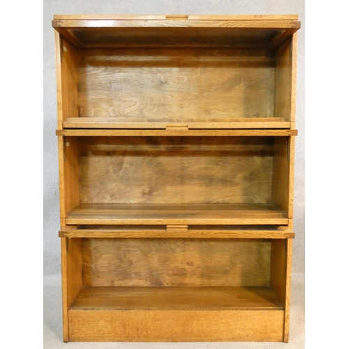 112 - A vintage light oak three section Globe Wernicke style bookcase with patent label for the Meovoto Ea...