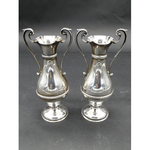 421 - A pair of Victorian twin scrolling handled silver urn vases with beaded detailing and scalloped rims...