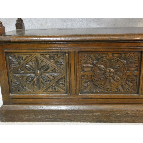 126 - A mid century carved oak monk's bench converting to centre table with lift up coffer section to the ...