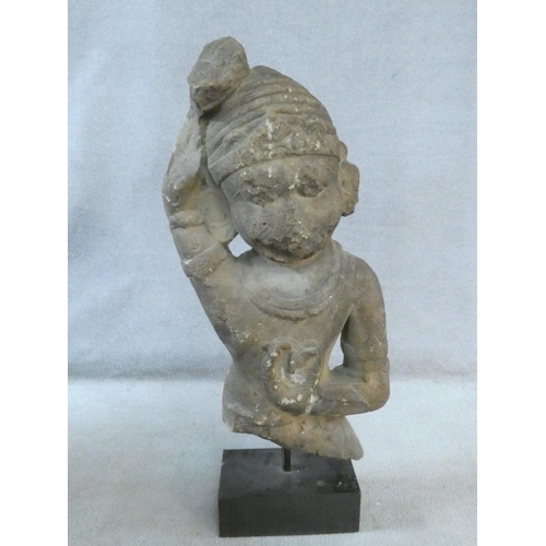 296 - A 14th/15th century South East Asian carved sandstone figure of a deity mounted on a square plinth. ...