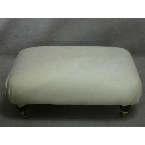 149 - A Multiyork footstool upholstered in jacquard fabric on turned tapering supports on brass cup caster...
