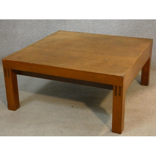 294 - A 1960's vintage teak coffee table on block supports. H.31 L.66 W.66cm