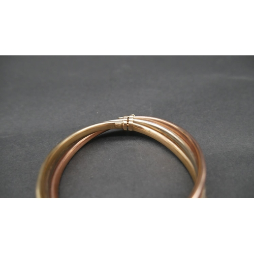 68 - A hollow three colour twist 9ct gold bangle with clip and loop clasp. Hallmarked. D.8cm, 15.5g