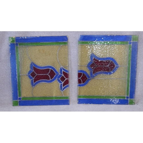 74 - An antique leaded stained glass panel with colourful stylised floral design. H.98 W.59cm (When toget...