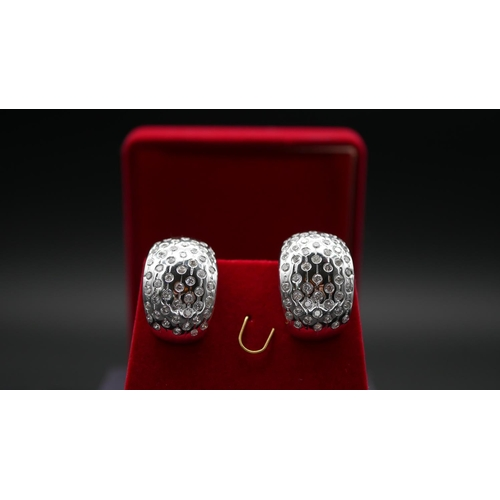 211 - A red velvet boxed pair of half hoop white metal (tested 18 carat white gold) and diamond pierced ea...
