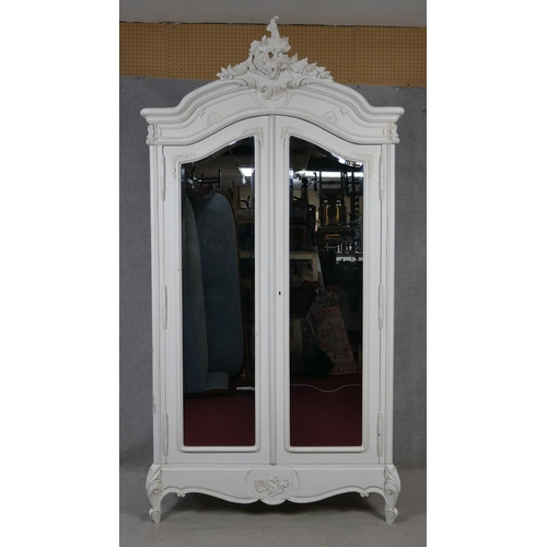 249 - A Louis XV style painted armoire with Rococo carved pediment above a pair of bevelled glass doors on...
