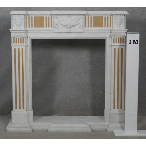 6 - A Classical style marble fire surround and hearth with carved urn decoration to the frieze flanked b...